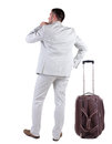 Back view of traveling busness man with suitcase looking up standing young guy in jeans and jacket rear people collection Stock Photo