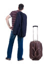Back view of traveling busness man with suitcase looking up standing young guy in jeans and jacket rear people collection Stock Photography