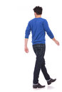 Back view of a walking casual man looking to a side on white background Royalty Free Stock Images