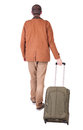 Back view of walking man with suitcase brunette guy in motion backside person in the airport luggage rear Royalty Free Stock Photos