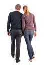 Back view of walking young couple man and woman going beautiful friendly girl and guy together rear view people collection Stock Photo