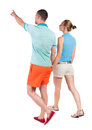 Back view of walking young couple man and woman pointing going tourists in shorts considering attractions rear people Royalty Free Stock Photography