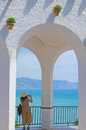 Back view of woman taking photo of seascape in nerja unrecognizable tourist making balcon de europa malaga andalusia spain Royalty Free Stock Image