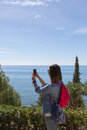 Back view of woman taking photo of waterscape adult brunette with pink backpack making with phone while standing against beautiful Royalty Free Stock Photos