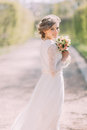 Back view of young blonde bride in white dress with bridal bouquet standing outdoor Royalty Free Stock Photo