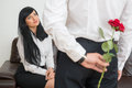 Back view of young businessman hiding a flower rose for his pretty colleague sitting on sofa in office and surprised looking at Royalty Free Stock Photos