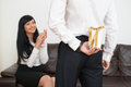 Back view of young businessman hiding gift box for while looking at and happy business lady in office with selective focus on Stock Photos