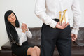 Back view of young businessman hiding gift box for in office while business lady is looking at his hand and waiting the Stock Image