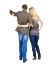 Back view of young couple pointing at wall. Stock Photos
