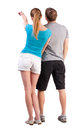 Back view of young couple pointing at wall woman and man rear view people collection backside view of person isolated over white Royalty Free Stock Image