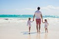 Back view of young father and his adorable little daughters walking on white sand beach in sunny day this image has attached Stock Images