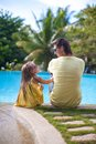 Back view of a young father and his cute daughter sitting near the swimming pool Stock Images