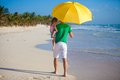 Back view of young father and his little daughter hiding from the sun under a yellow umbrella this image has attached release Royalty Free Stock Photography