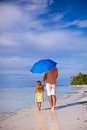 Back view of young father and his little daughter walking under a blue umbrella this image has attached release Royalty Free Stock Photo