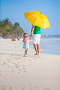 Back view of young father and his little daughter walking under a yellow umbrella this image has attached release Stock Photo