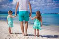 Back view of young father and his two little kids walking by the sea this image has attached release Royalty Free Stock Image