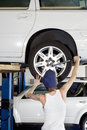 Back view of young female working on car tire in workshop Stock Image