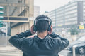 Back view of a young man with headphones posing in the city stre Royalty Free Stock Photo