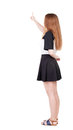 Back view of young redhead woman pointing at wall beautiful gir girl in dress rear people collection backside person Royalty Free Stock Photos