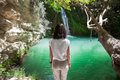 Back view of young woman enjoy waterfall on beautiful lake Royalty Free Stock Photo