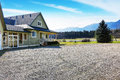 Back yard green house with porch. Gravel driveway Royalty Free Stock Photo