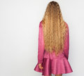 Back of the young woman with long blond curly hair with healthy shine, wearing a purpl dress over a studio background. Royalty Free Stock Photo