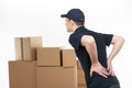 Backache young deliveryman standing with his hands on back and feeling pain Royalty Free Stock Photos
