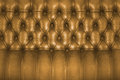 Backboard of a vintage golden brown chesterfield sofa Stock Photos