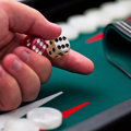 Backgammon player's hand holding the dice square Royalty Free Stock Photo