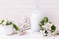 Background with apple blossom candle in decorative bird cage an and heart on white painted wooden planls selective focus Stock Photography