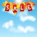 Background autumn sale maple leaves with the word on a of blue sky and clouds Stock Images