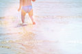 Background of blue sea with little baby's legs in water. Holidays with kids. Summer beach. Adorable child can be boy or girl Royalty Free Stock Photo