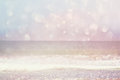 Background of blurred beach, sea waves and sailing boat at horizon with bokeh lights, vintage filter.