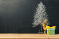 Background with Christmas tree drawing on chalkboard and gift box Royalty Free Stock Photo