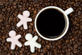 Background of coffee beans with cup of black coffee and sugar in the form little men top view Stock Photo