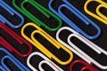 Background with colored paperclips on black ground Stock Images