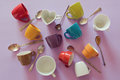 Background with colorful empty coffee cups and spoons. View from above