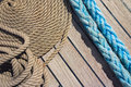 Background deck sailing ship thick rope in spiral or ring shape on a wooden floor Stock Photos