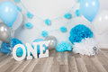 background decoration for birthday celebration with gourmet cake, letters saying one and blue balloons in studio Royalty Free Stock Photo
