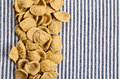 Background of dry pasta orecchiette brown on striped fabric Stock Photos