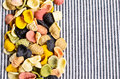 Background of dry pasta orecchiette different colors on striped fabric Stock Images