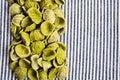 Background of dry pasta orecchiette green striped fabric Stock Photo
