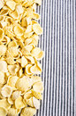 Background of dry pasta orecchiette white striped fabric Royalty Free Stock Photo