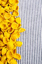 Background of dry pasta orecchiette yellow striped fabric Royalty Free Stock Image