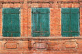 Background image of three old green bolted shuttered windows Royalty Free Stock Photo