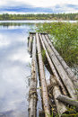 Background landscape forest lake under a cloudy sky with old wooden footbridges Royalty Free Stock Photo