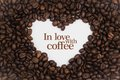 Background made of coffee beans in a heart shape with message `In love with coffee`