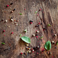 Background of peppercorns and basil scattered on an old weathered wooden surface after preparing seasoning a meal Royalty Free Stock Photo