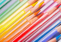 Background of rainbow coloured pencils wooden pencil crayons arranged diagonally with a close up view the tips Royalty Free Stock Photos