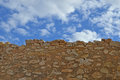 Background of a stone wall and cloudy sky an old under partly for use as or backdrop Stock Photography